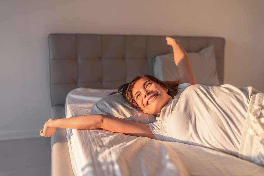 Young woman waking up happy and refreshed