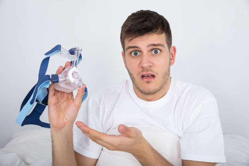 Young Man Holding CPAP Machine